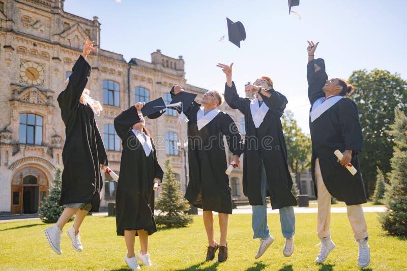 Kończący studia uczni skacze wysoko z ich nakrętkami zdjęcia stock