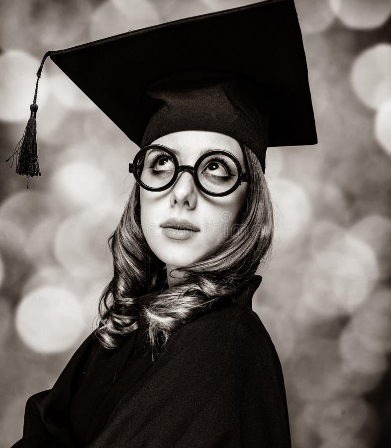 Kończyć studia studenckiej dziewczyny w akademickiej todze obrazy stock