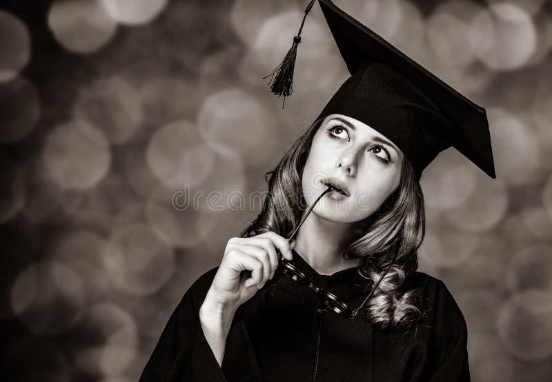 Kończyć studia studenckiej dziewczyny w akademickiej todze fotografia stock