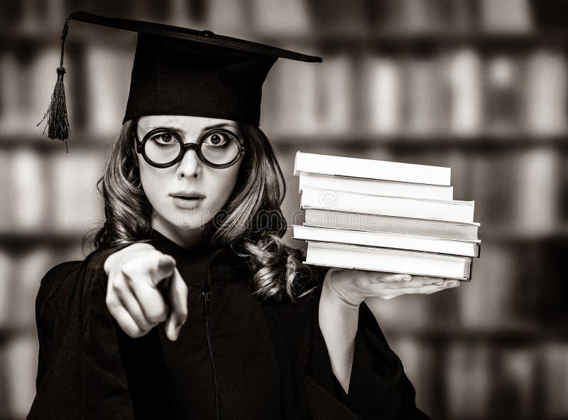 Kończyć studia studenckiej dziewczyny w akademickiej todze z książkami zdjęcie stock