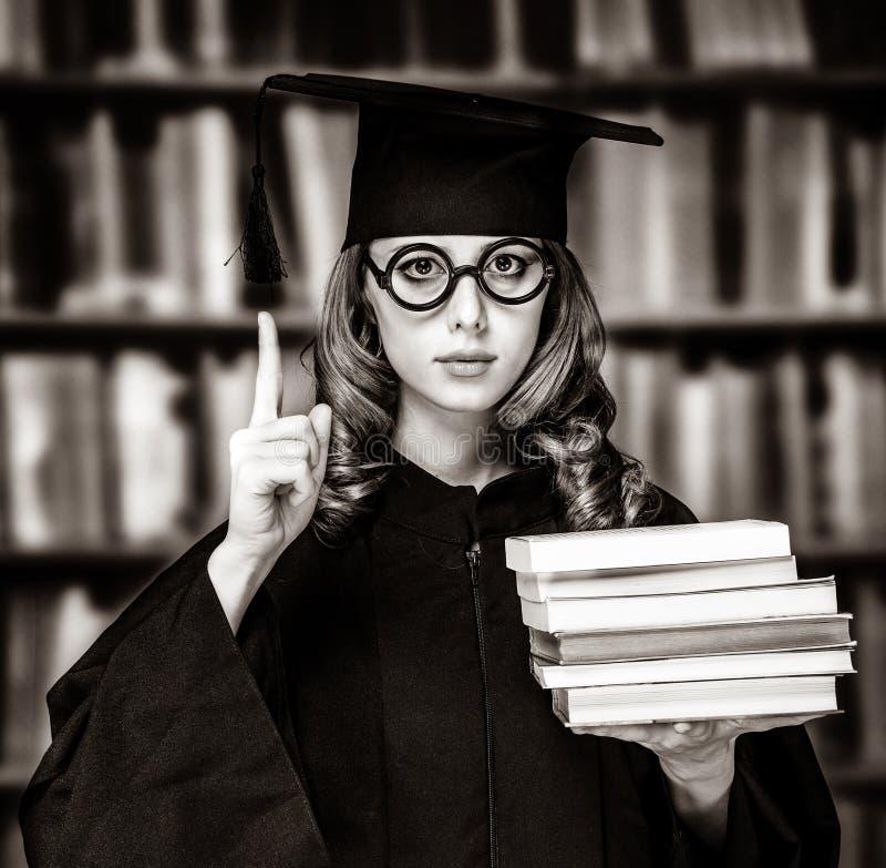 Kończyć studia studenckiej dziewczyny w akademickiej todze z książkami obrazy royalty free