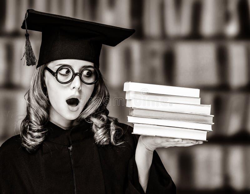 Kończyć studia studenckiej dziewczyny w akademickiej todze z książkami obraz royalty free