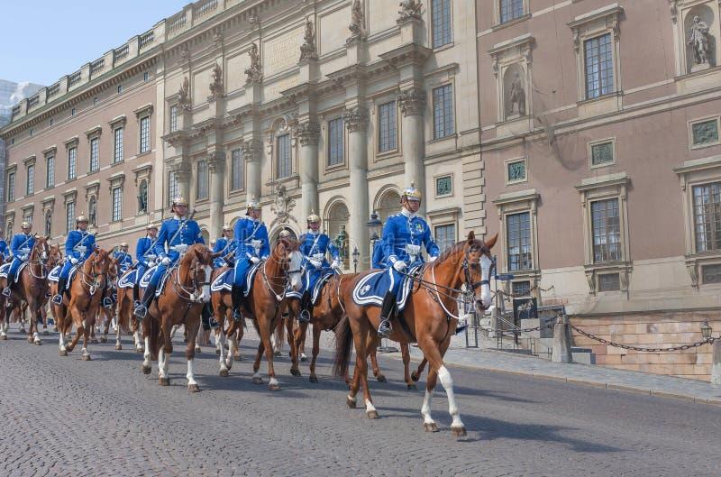Końscy jeźdzowie od Wspinających się Królewskich strażników w mundurach zbliżają pałac królewiątko zdjęcie royalty free