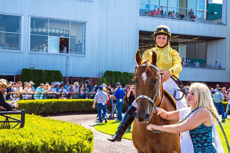 Koński i żeński dżokej dostaje przygotowywający dla rasy przy szmaragdem Zestrzela fotografia royalty free