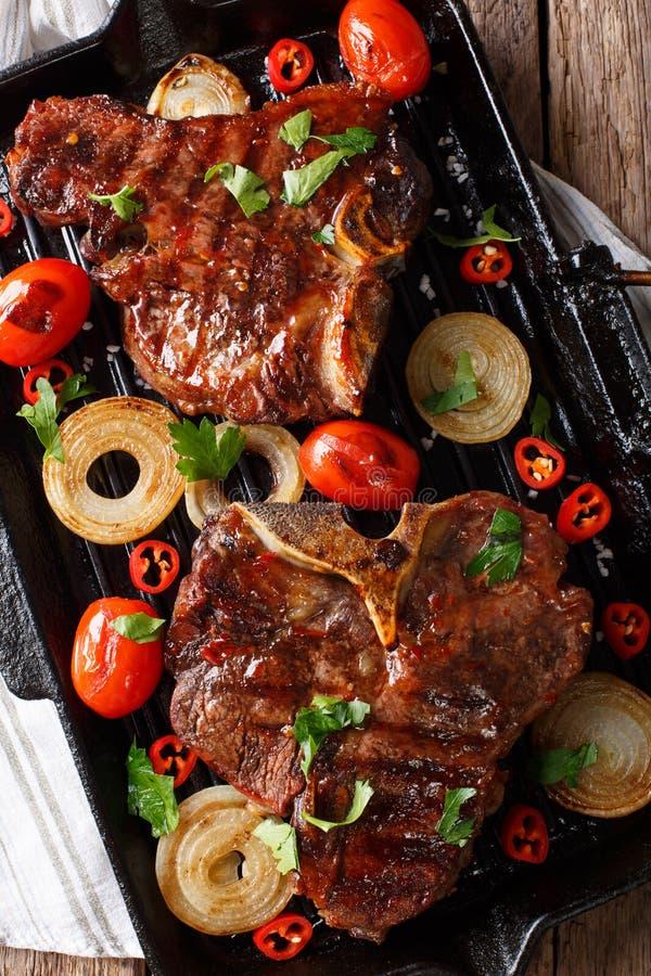 kość stek z pomidorami i cebulami w grillu smaży niecek clos zdjęcia royalty free