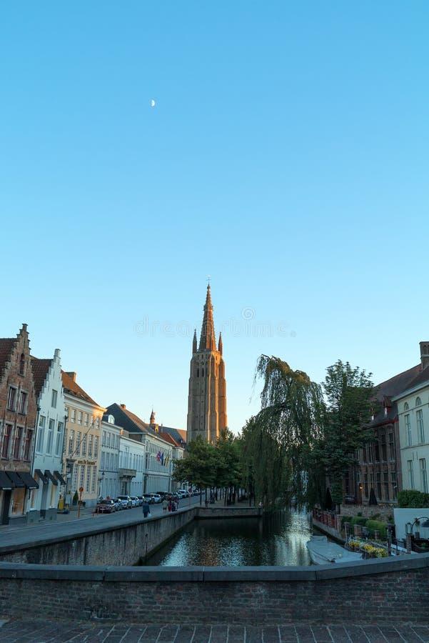 Kościół Nasz piękna wąska ulica z kanałem w Bruges i dama, Belgia zdjęcia stock