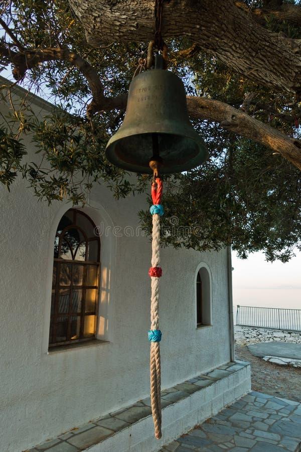 Kościelny dzwon przed ażio Ioannis Kastri kościół przy zmierzchem, sławnym od Mamma Mia filmu scen, Skopelos wyspa obraz stock