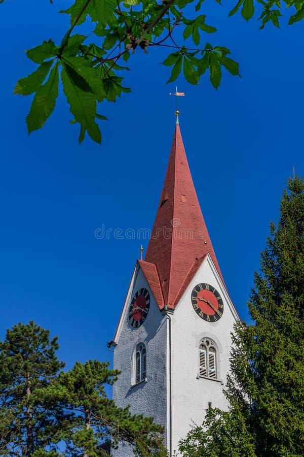 Kościelny wierza z zegarem przeciw niebieskiemu niebu i drzewom zdjęcie royalty free
