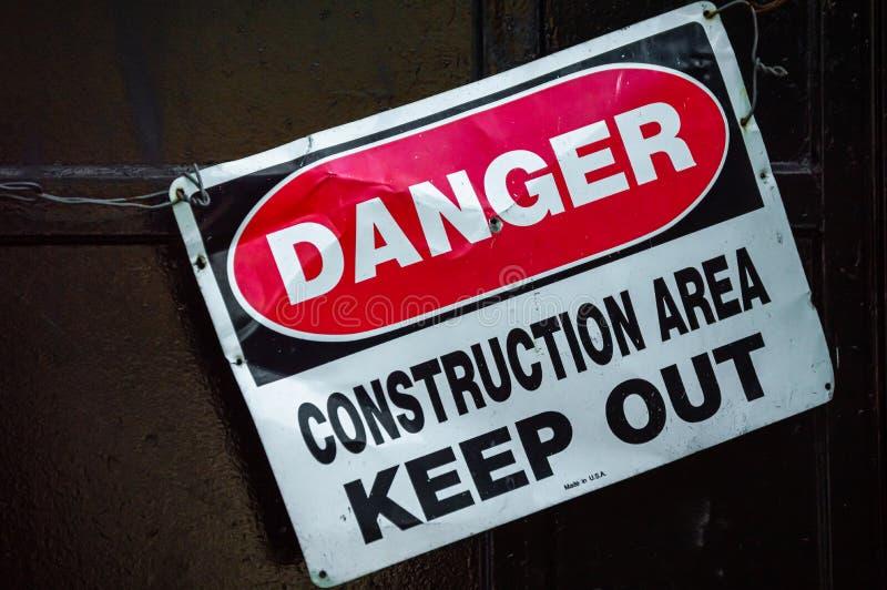 Koślawy stary metalu znak ostrzegawczy który czyta niebezpieczeństwo budowy teren UTRZYMUJE ZA obraz royalty free