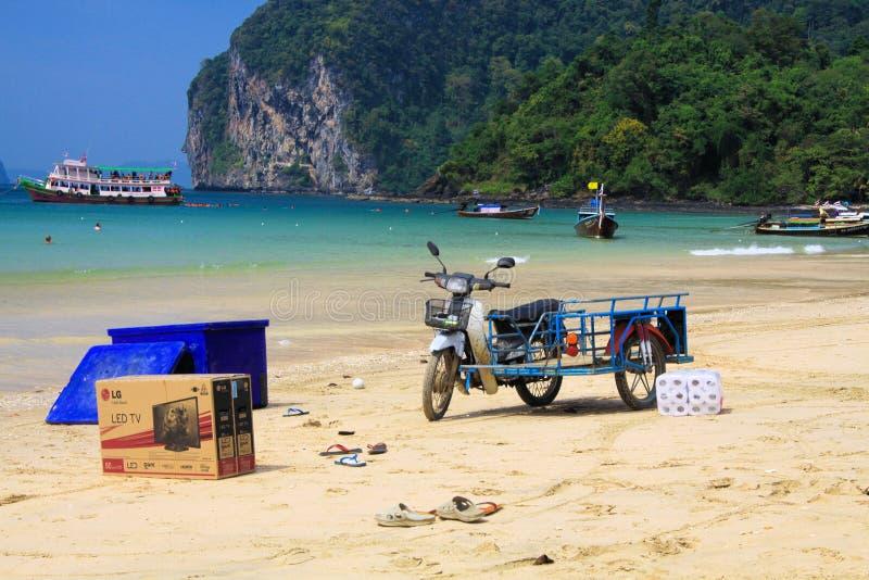 KO MOK, TAJLANDIA ANDAMAN morze - GRUDZIEŃ 28 2013: Odosobniony motocykl na plaży z towarami dostarczać daleką tropikalną wyspę zdjęcia stock