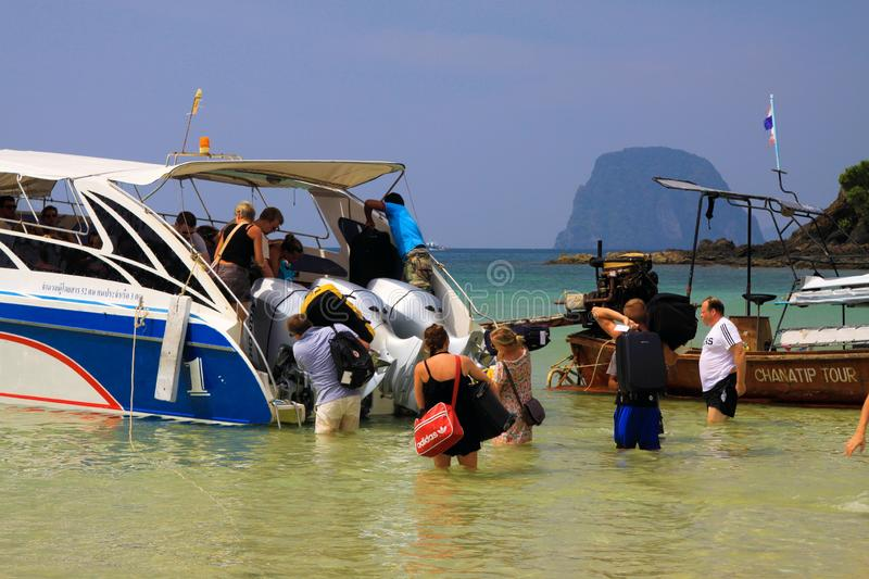 KO MOK, THAILAND ANDAMAN SEA - DECEMBER 28. 2013:Tourists enter speed boat to leave tropical island royalty free stock image
