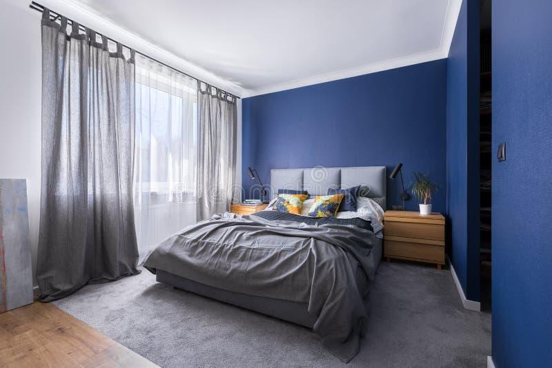 Kobaltblauschlafzimmer mit Bett stockfotografie