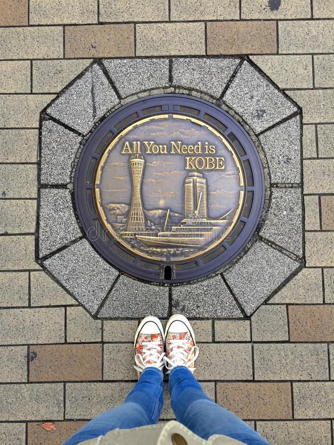 Female feet wearing sneakers standing in front of typical decorated Manhole of Kobe City, Japan. Kobe, Hyogo, Japan - 29th October 2018 : Top view on female feet stock photography
