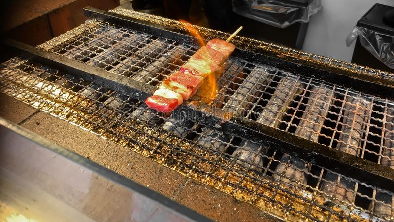 Kobe Japanese premium beef charcoal grilled skewer on fire. Smells really good royalty free stock images