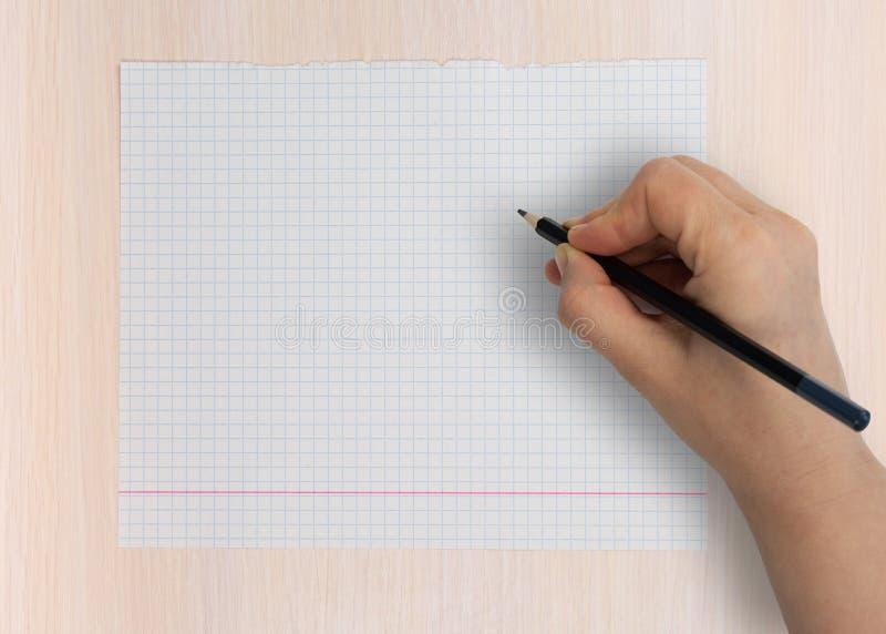 Kobieca dłoń pisze ołówkiem na pustym arkuszu fotografia stock