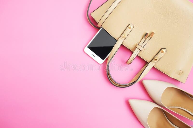 Kobiecy akcesoria mieszkanie nieatutowy Kobieta butów torby smartphone na różowym tle Beżowi kolor kobiety akcesoria Tekst przest fotografia stock