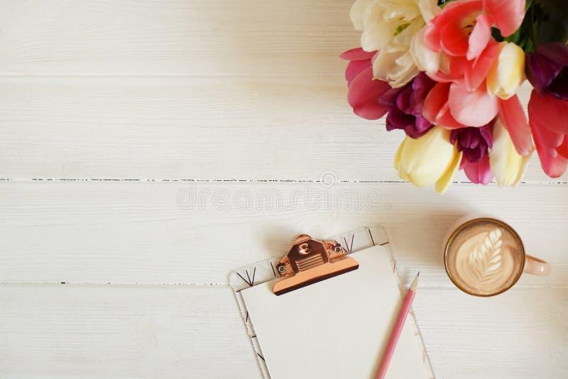 Kobiecy desktop skład z pustego prześcieradła schowkiem, ołówek, filiżanka, tulipanu bukiet, drewniany stołowy tło Kobiety workpl zdjęcie royalty free