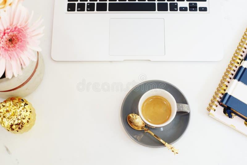 Kobiecy miejsca pracy pojęcie w mieszkanie nieatutowym stylu z laptopem, kawa obraz royalty free