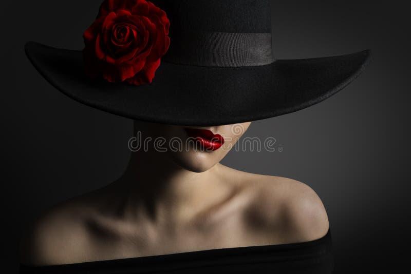 Kobiet Czerwone wargi i róża kwiat w czarnym kapeluszu, piękno mody model obraz royalty free