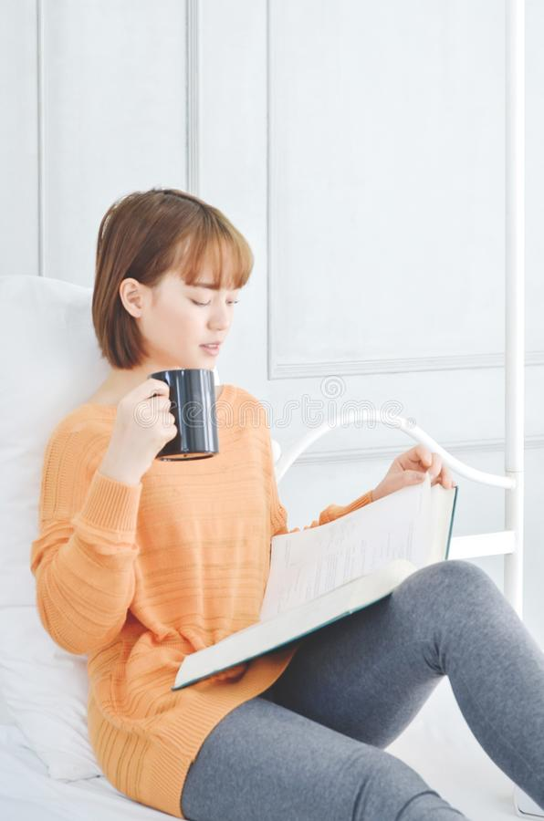 Kobiet czytelnicze książki i pić kawa fotografia royalty free