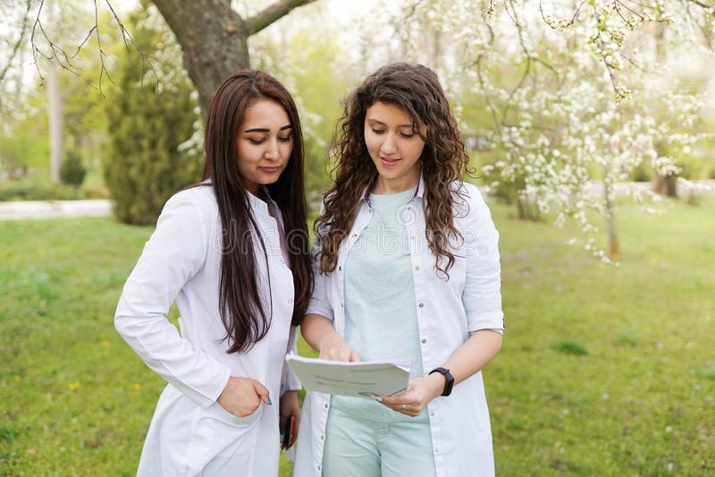 Kobiet lekarki outdoors mapy t?a oko medical optometrist ucznie blisko szpitala w kwiatu ogr?dzie zdjęcia royalty free