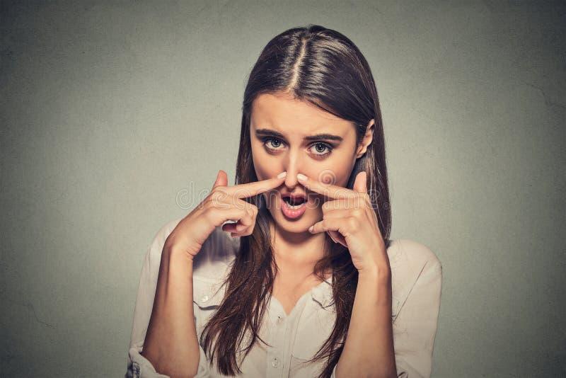 Kobiet nękań nos z palec ręk spojrzeniami z obmierzłością coś śmierdzi zdjęcie royalty free