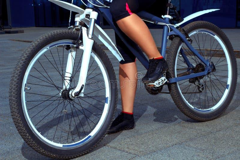 Kobiet nogi w ciasnym odziewają z bicyklem fotografia stock