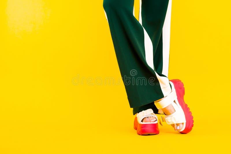Kobiet nogi w sportów sandałach z czerwonymi podeszwami i zieleni spodniami z lampasami fotografia stock