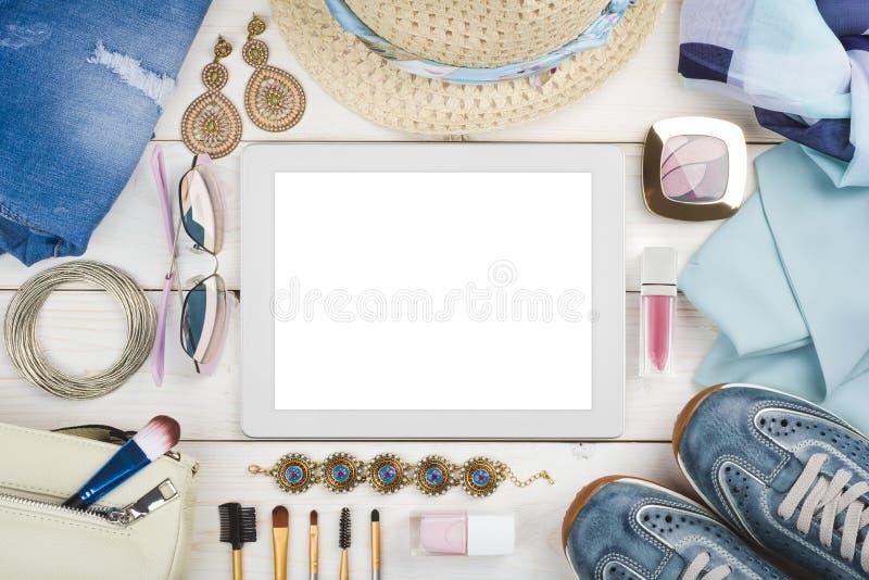Kobiet odziewać, akcesoria i kosmetyk na drewnie wokoło pastylka komputeru, obrazy stock
