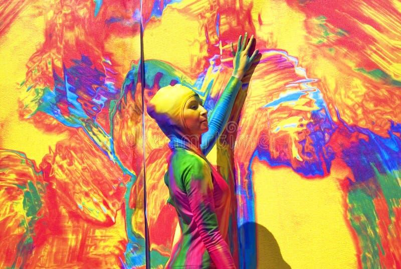 Kobiet pozy dla fotos przy kolorowym tłem