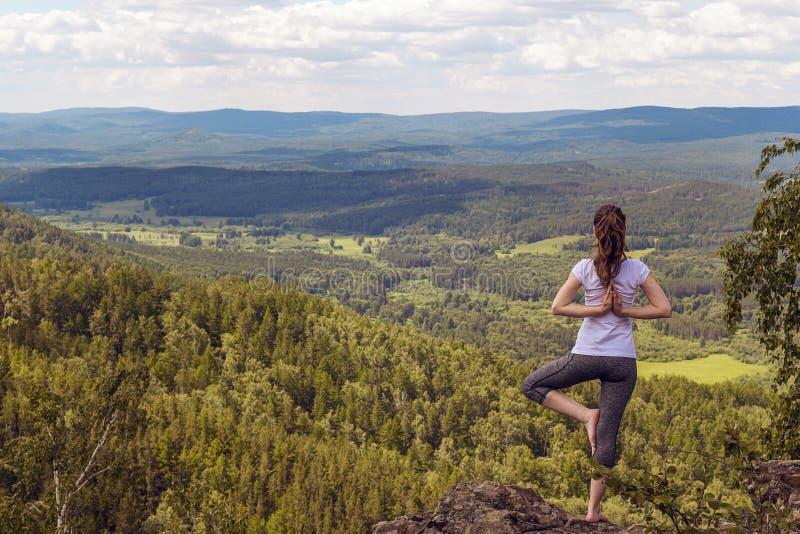 Kobiet praktyk joga balansowego asana Vrikshasana drzewna poza w moun obraz royalty free