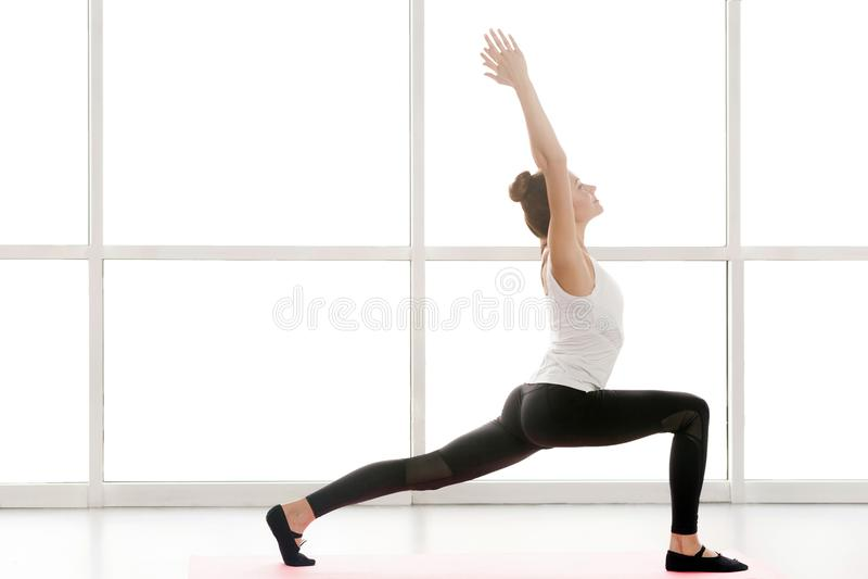 Kobiet przyglądający up, ręki up i robić joga, wojownika jeden postura zdjęcia royalty free