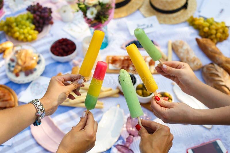 Kobiet ręk chwyta kolorowy lody wtyka przy lato pinkinu tłem Lato weekendy zdjęcie stock