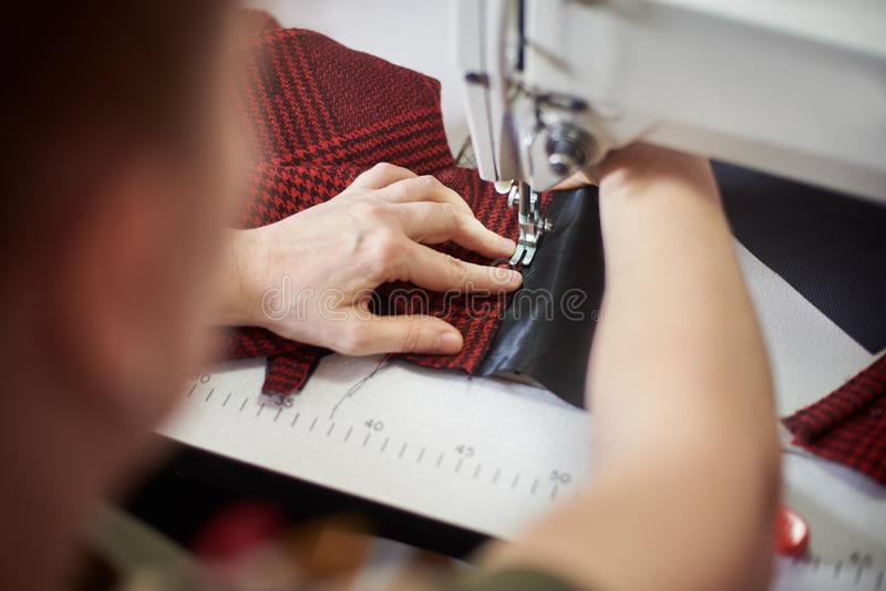 Kobiet ręki przy szwalną procesu i naprawianie szkockiej kraty tkaniną na fachowej rękodzielniczej maszynie Zamyka w górę widok obrazy stock