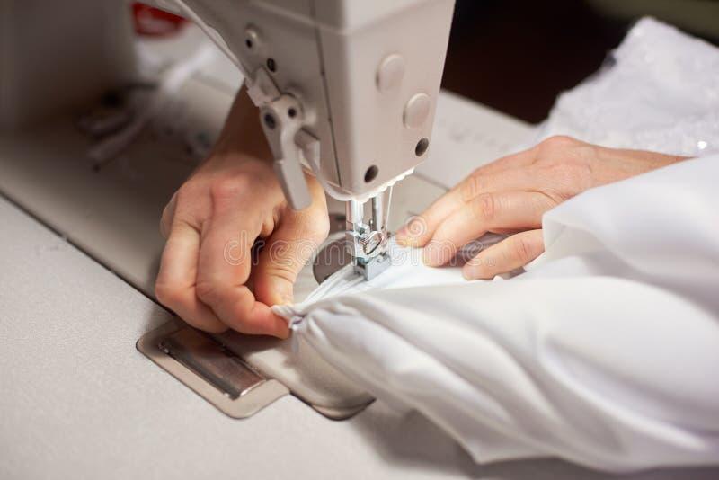 Kobiet ręki przy szwalnym procesem i naprawiać białą tkaninę na fachowej rękodzielniczej maszynie Zamyka w górę odgórnego widoku zdjęcie royalty free