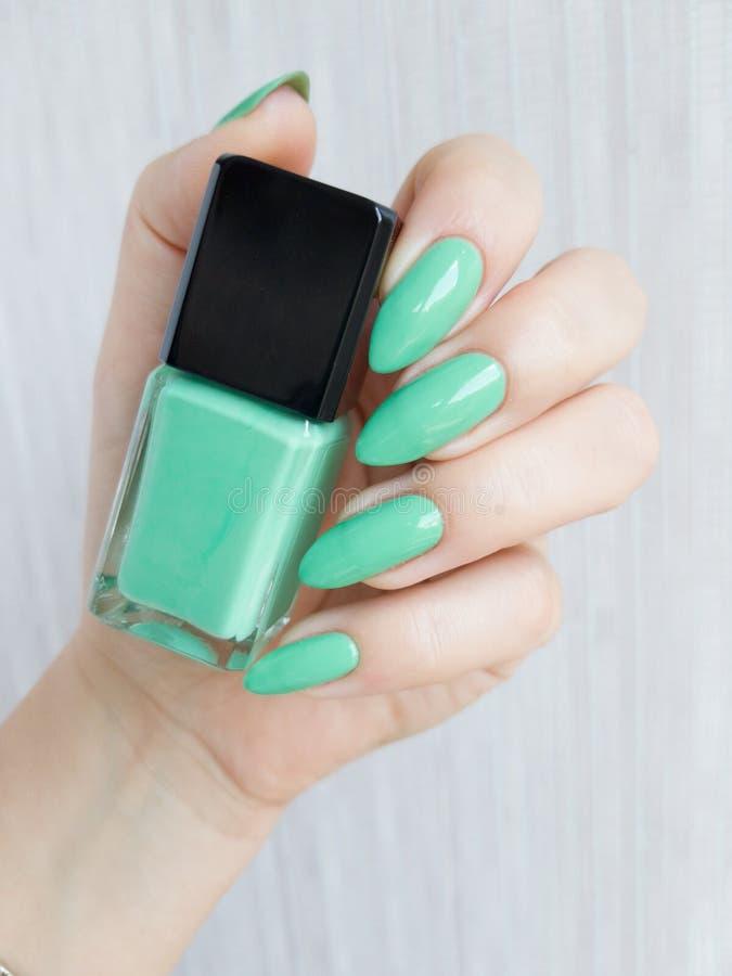 Kobiet ręki z długimi gwoździami z zielonym gwoździa połyskiem fotografia royalty free