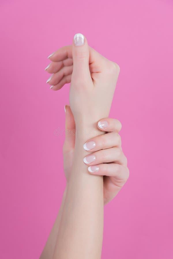 Kobiet ręki z francuskimi gwoździami robią manikiur styl odizolowywającego na różowym tle fotografia stock