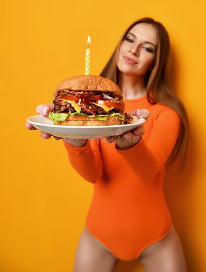 Kobiet ręk chwyta hamburgeru grilla duża kanapka z wołowiną i zaświecającą świeczką dla przyjęcia urodzinowego na kolorze żółtym obraz royalty free