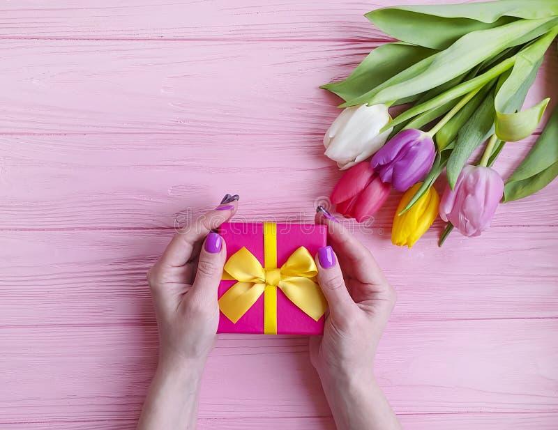 Kobiet ręk chwyta rocznicowy piękno prezenta pudełka marszu wakacyjny urodziny, przedstawia bukiet tulipany na różowym drewnianym obrazy royalty free