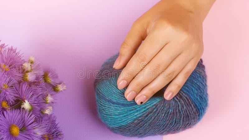 Kobiet ręk opieka Piękno kobiety gwoździe Czyści menchia gwoździe Ręka z sercem na kolorowym tle z kwiatami opieki ostrości ręki  fotografia royalty free