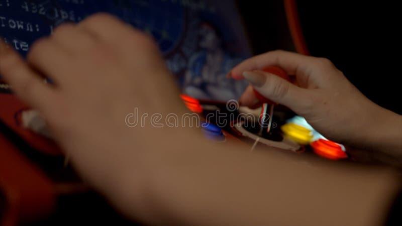 Kobiet ręki bawić się automat do gier akcja W górę młodej kobiety entuzjastycznie bawić się automat do gier z guzikami obraz stock