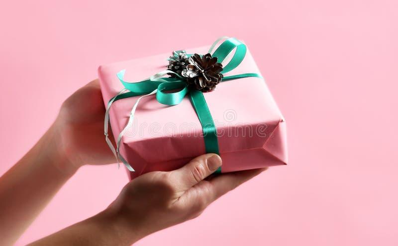 Kobiet ręki dają Bożenarodzeniowej teraźniejszości prezentowi dla nowego roku 2019 na świetle - menchia obrazy royalty free