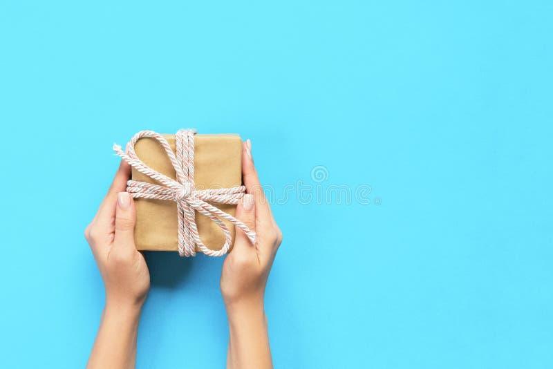 Kobiet ręki dają zawijającego valentine lub innej wakacyjnej handmade teraźniejszości w papierze z błękitnym faborkiem Teraźniejs obrazy stock
