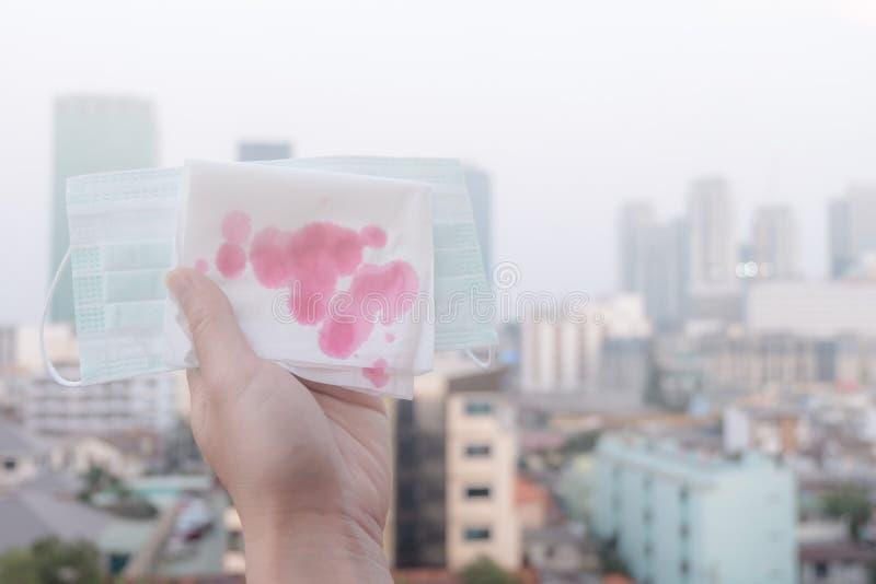 Kobiet ręki lub kobiet ręki trzyma przez zanieczyszczenie powietrza w mieście ochronną maskę pieluchę z krwią i szczególnego zdjęcie royalty free