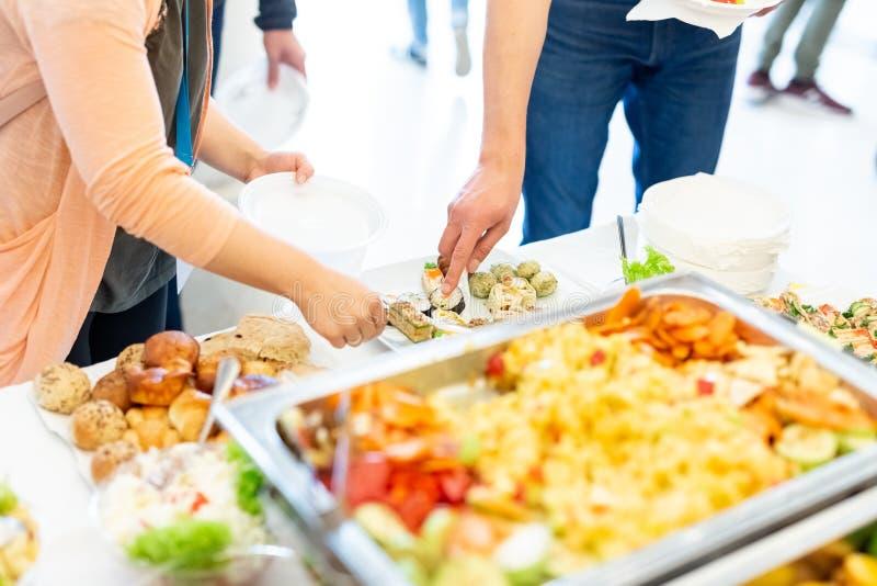 Kobiet ręki podnosi w górę jedzenia od półmiska Wydarzenie bufeta ślubny pojęcie obrazy stock