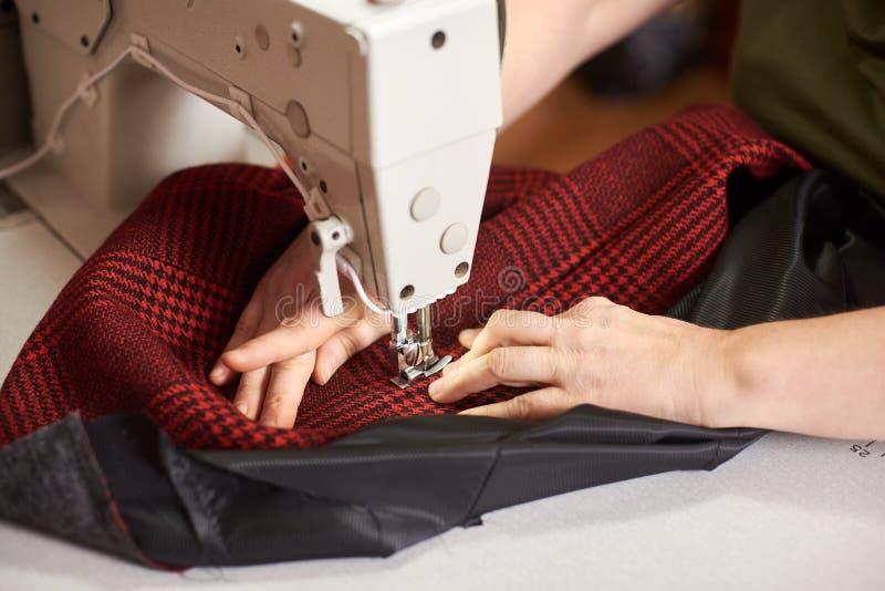 Kobiet ręki przy szwalną procesu i naprawianie szkockiej kraty tkaniną na fachowej rękodzielniczej maszynie Zamyka w górę widok fotografia royalty free