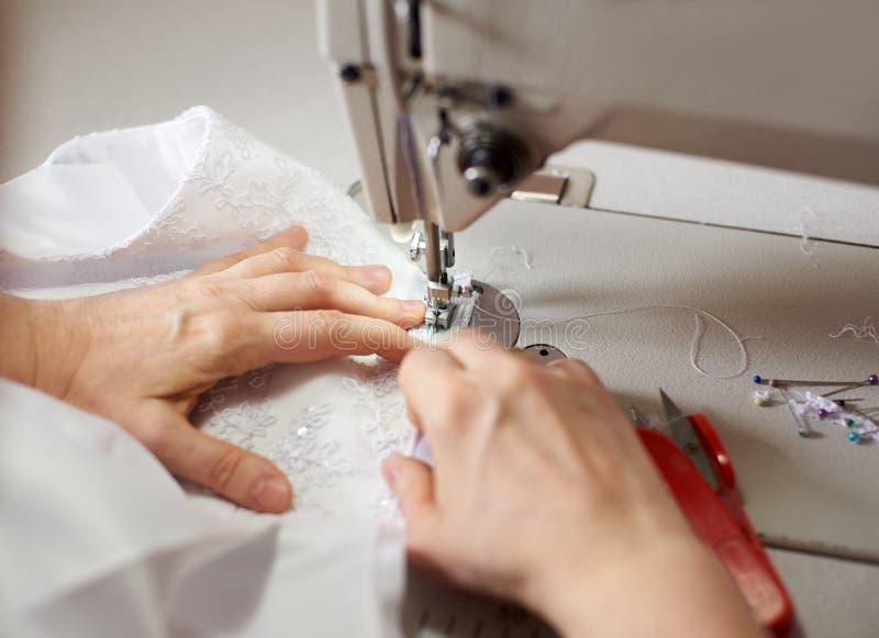Kobiet ręki przy szwalnym procesem i naprawiać białą tkaninę na fachowej rękodzielniczej maszynie Zamyka w górę makro- widoku zdjęcia royalty free