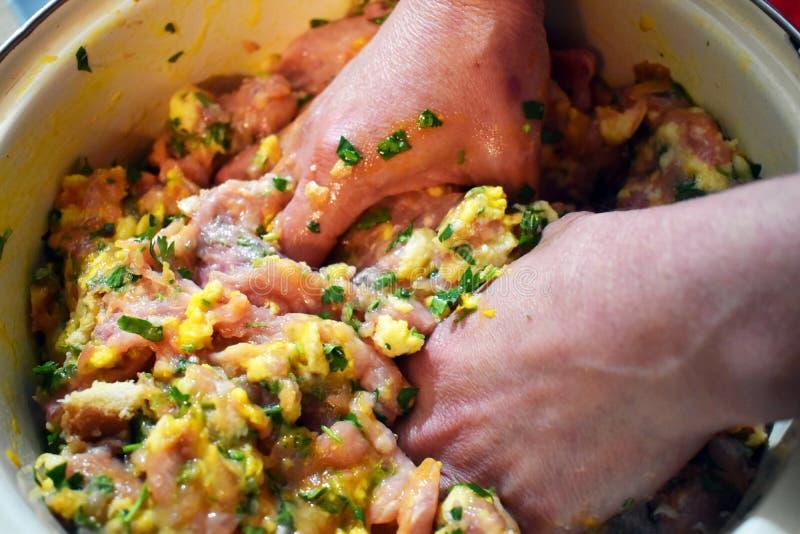 Kobiet ręki przygotowywają miced świeżego mięso dla klopsików Ręcznie mieszać mięso z jajkami, pietruszką i czosnkiem, fotografia stock