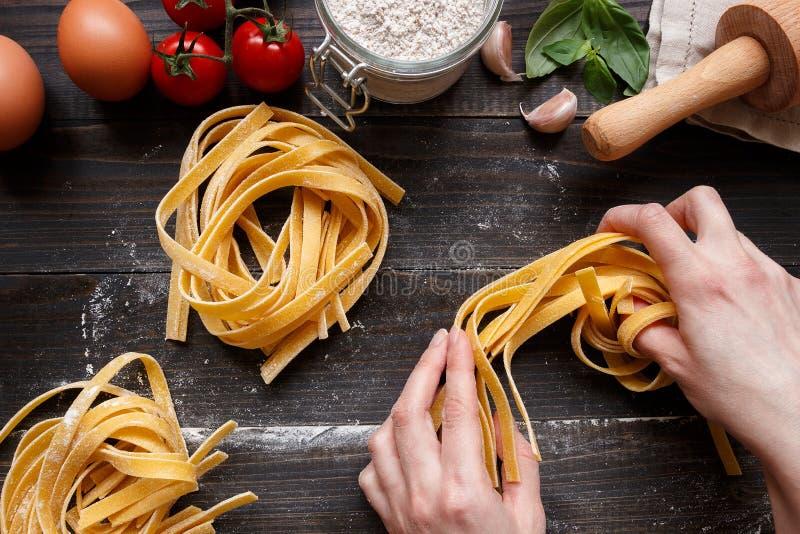 Kobiet ręki robi świeżemu domowej roboty makaronowi Makaronów składniki na ciemnym drewnianym stołowym odgórnym widoku zdjęcie stock