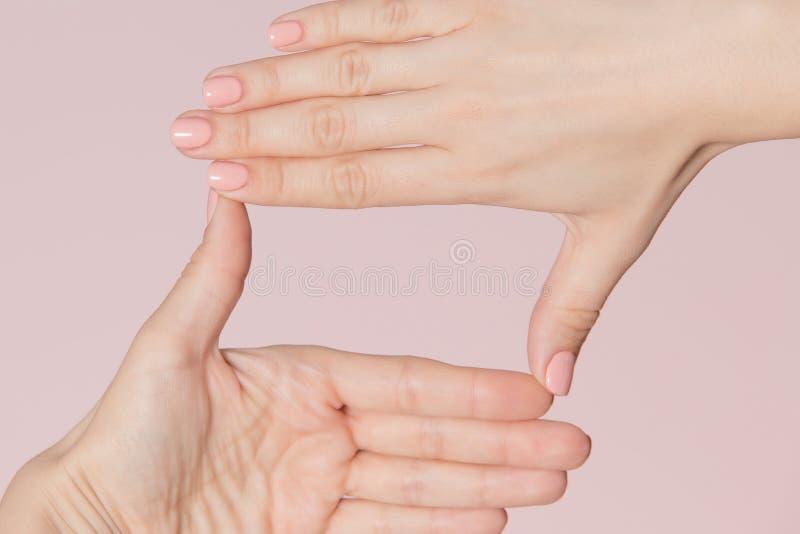 Kobiet ręki robi kwadrat ramie odizolowywającej na różowym tle Manicure reklama obraz royalty free